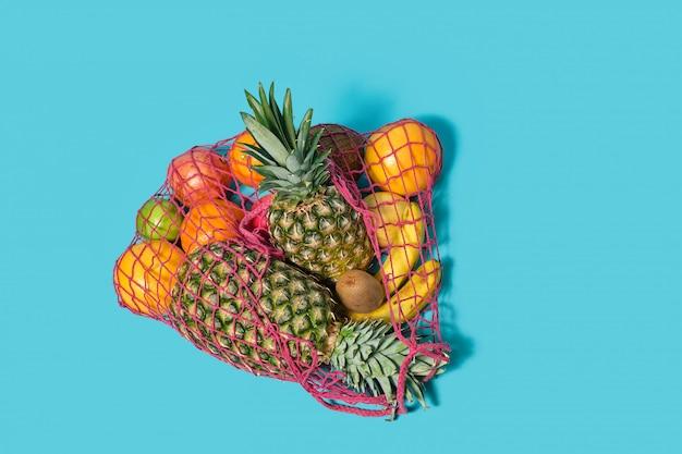 Tropische vruchten liggen in een string zak op een blauwe tafel. ecologische voetafdruk concept.