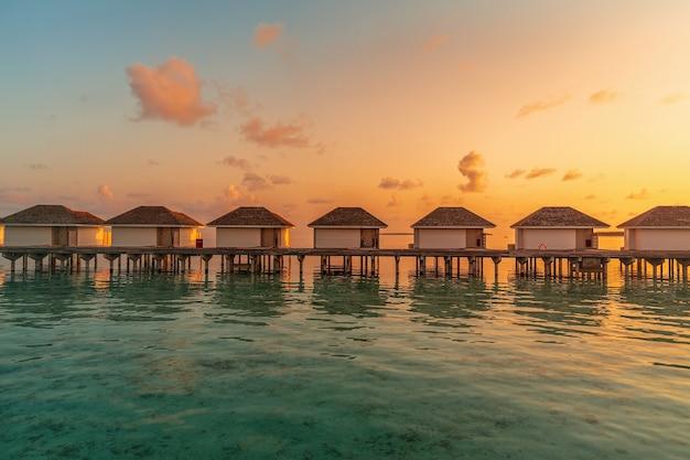 Tropische watervilla's met bezinning over het eiland van de maldiven in zonsopgangtijd
