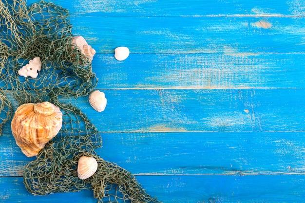 Tropische zee achtergrond. verschillende schelpen, oude visnet op de blauwe planken, bovenaanzicht. vrije ruimte voor inschrijvingen. zomer thema.