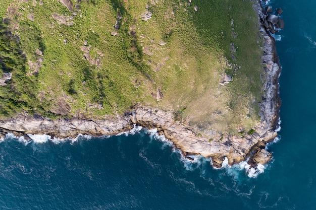 Tropische zee met golf crashen op kust en hoge berg gelegen