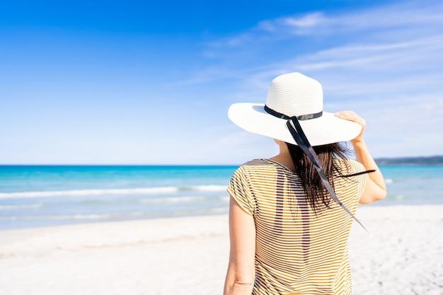Tropische zee reizen adv banner stijl onherkenbare vrouw met witte grote hoed met een hand