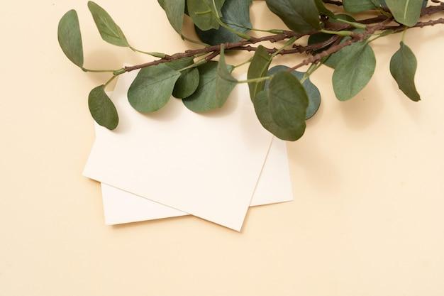 Tropische zomer briefpapier mock-up scene. blanco visitekaartje, groene eucaliptusbladeren, beige getextureerde tabelachtergrond. platliggend, bovenaanzicht