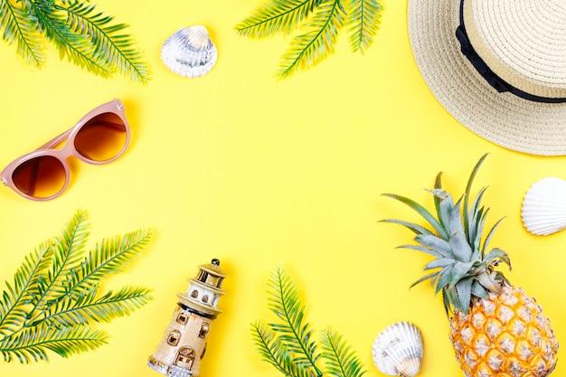 Tropische zomer concept met vrouw mode-accessoires, bladeren en ananas op gele achtergrond. plat lag, bovenaanzicht