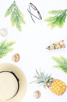 Tropische zomer concept met vrouw mode-accessoires, bladeren en ananas op witte achtergrond. plat lag, bovenaanzicht