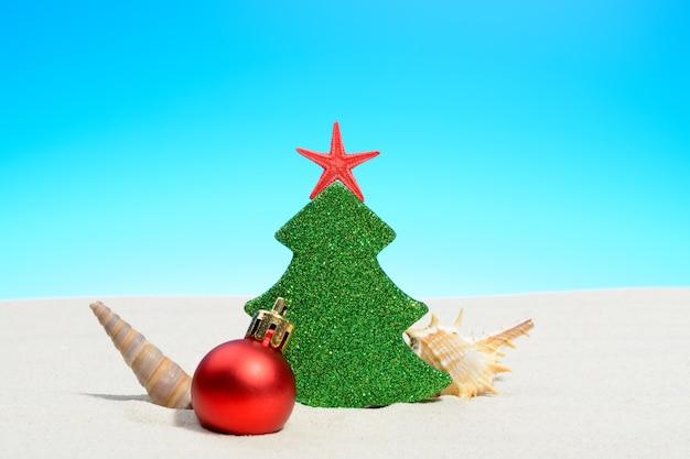 Tropische zomer strand kerstmis met een kerstboom, een kerstbal en schelpen op goudkleurig zand en kopieer ruimte voor uw groet op blauwe hemel