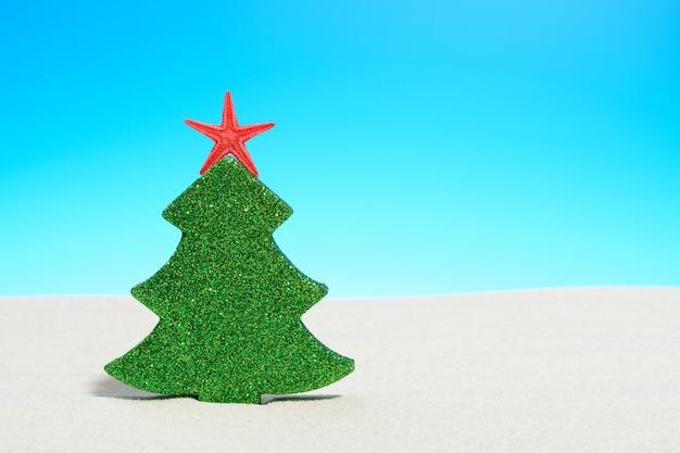 Tropische zomer strand kerstmis met een kerstboom op zand en kopieer ruimte voor uw groet op blauwe hemel