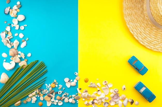Tropische zomer strand reizen concept. palm tree leaf, strooien hoed, zeeschelp, blauwe auto op geel. kopieer ruimte.