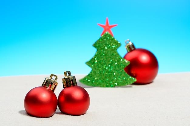 Tropische zomerstrand kerstmis met een kerstboom, kerstbal op goudkleurig zand en kopieer ruimte voor uw groet op blauwe hemel