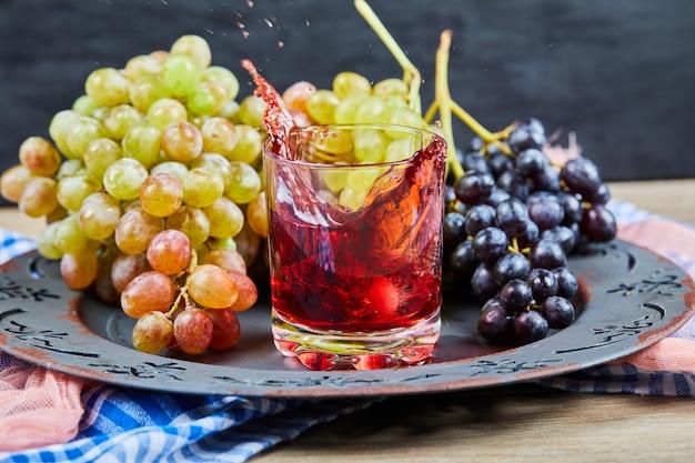 Tros druiven en een glas sap op zwart.