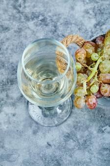 Tros druiven en een glas wijn op blauw.