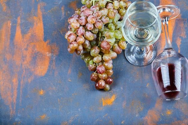 Tros druiven en glazen wijn op blauw.