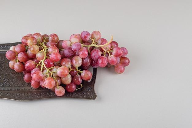 Trossen druiven en een sierlijk dienblad op marmer