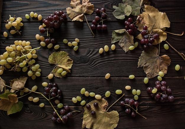 Trossen witte en donkere druiven, droge bladeren op het donkere houten oppervlak. bovenaanzicht