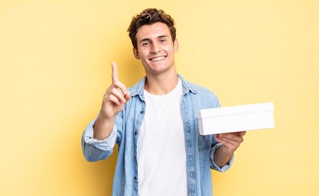 Trots en zelfverzekerd glimlachen en nummer één triomfantelijk poseren, voelend als een leider. witte doos concept