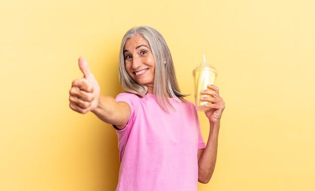 Trots, zorgeloos, zelfverzekerd en gelukkig voelen, positief glimlachen met duimen omhoog en een milkshake vasthouden