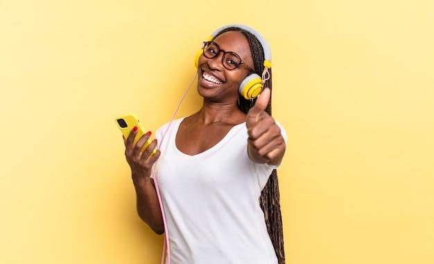 Trots, zorgeloos, zelfverzekerd en gelukkig voelen, positief glimlachen met duimen omhoog en muziek luisteren