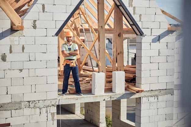 Trotse arbeider met een helm terwijl hij met zijn armen gekruist staat in het onvoltooide gebouw