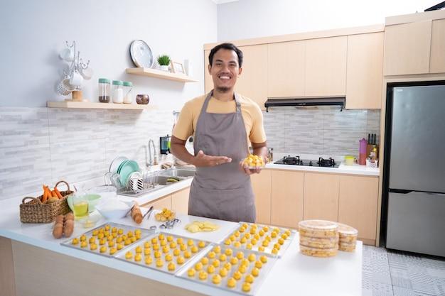 Trotse aziatische jonge man met zijn koken glimlachen. thuis nastar-cake maken voor eid mubarak. kleine ondernemer met zijn product
