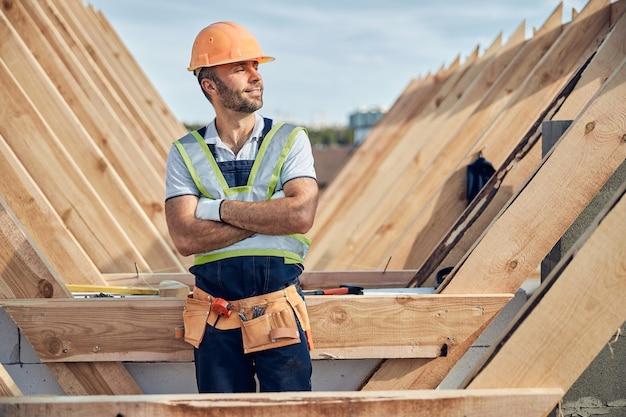 Trotse bouwer met een helm die er tevreden uitziet met zijn werk terwijl hij met zijn armen gekruist op een bouwplaats staat