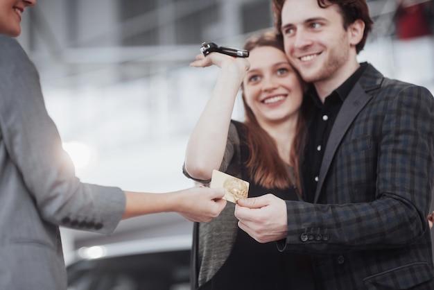 Trotse eigenaars. het mooie jonge gelukkige paar koesteren die zich dichtbij hun onlangs gekochte auto bevinden die vreugdevol het tonen van autosleutels glimlachen aan de camera
