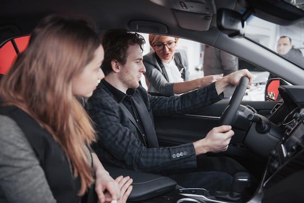 Trotse eigenaars. het mooie jonge gelukkige paar koesteren die zich dichtbij hun onlangs gekochte auto bevinden die vreugdevol tonend autosleutels copyspace familielevensstijl het kopen consumentisme glimlachen