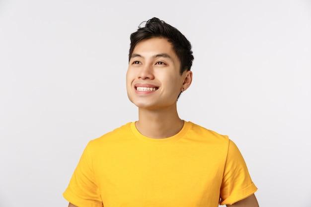 Trotse en dromerige knappe zelfverzekerde en vrolijke aziatische man, draag geel t-shirt, lachend opgetogen en overweeg iets moois in de linkerbovenhoek, witte muur