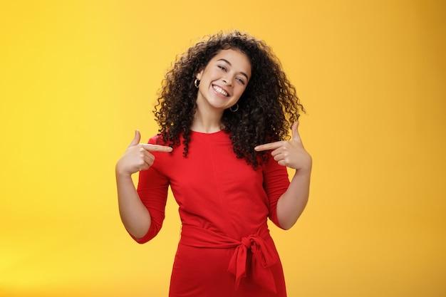 Trotse en tevreden ambitieuze succesvolle vrouwelijke student in rode jurk die tevreden glimlacht en naar zichzelf wijst alsof ze blij en blij opschept over eigen prestaties over de gele muur.