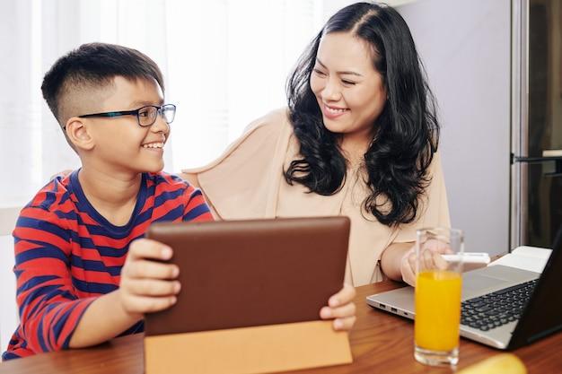 Trotse glimlachende zoon die tabletcomputer toont aan motehr na het beëindigen van het harde niveau in het spel
