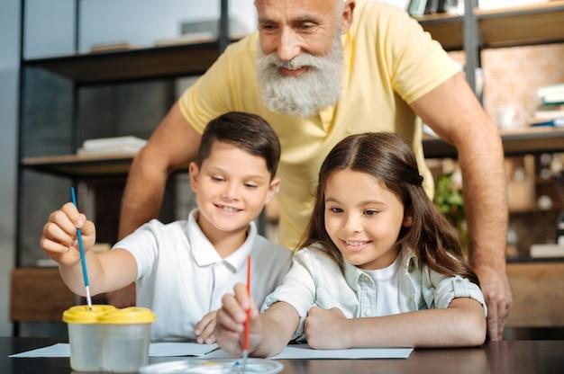 Trotse grootvader. gelukkige oudere man die achter zijn geliefde kleinkinderen staat en kijkt hoe ze de borstel in een waterbak wassen en een kleur kiezen uit het palet