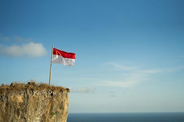 Trotse indonesische man op een strandklif die de rode en witte vlag van indonesië opheft