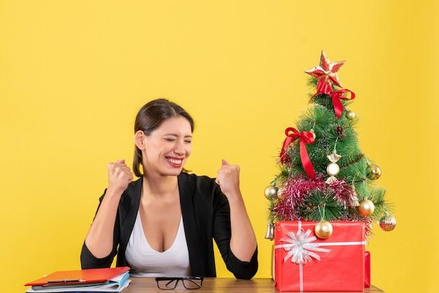 Trotse jonge vrouw in pak met versierde kerstboom op kantoor op geel