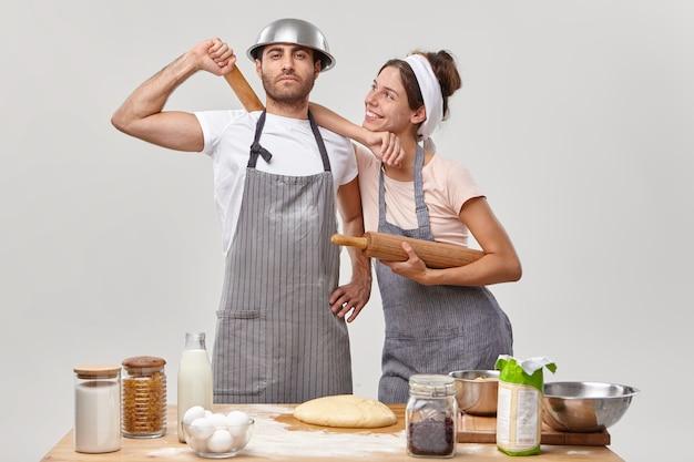 Trotse man en zijn vrolijke vrouw druk in de keuken, gekleed in schorten, deeg maken, samen brood bakken, geheime ingrediënt gebruiken, tegen een witte muur bij de tafel staan met verse producten
