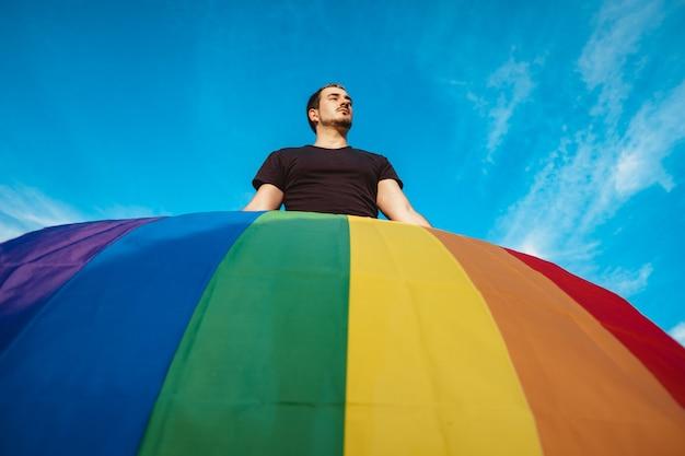 Trotse man met homo-regenboogvlag die op de wind zwaait, conceptfoto over mensenrechten en gelijkheid