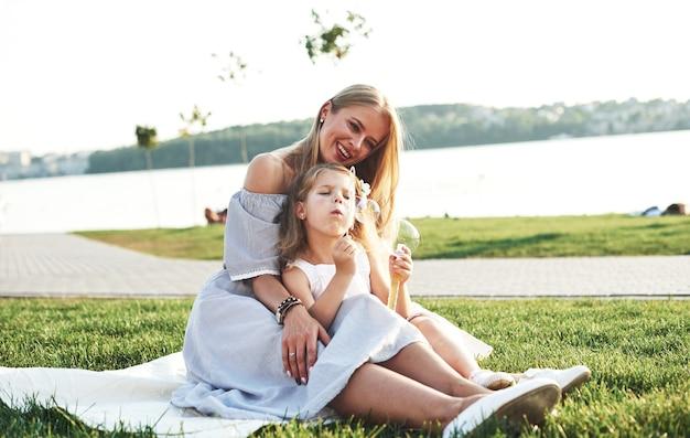Trotse moeder kijkt naar dochter. foto van jonge moeder en haar dochter die goede tijd hebben op het groene gras met meer bij achtergrond.