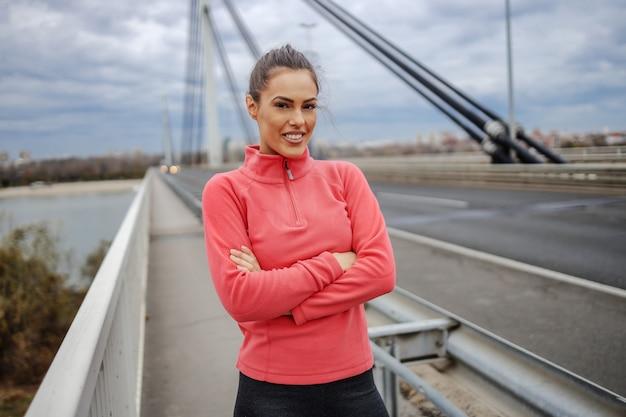 Trotse mooie lachende sportvrouw in sportkleding staande op de brug met gekruiste armen