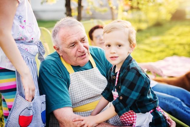 Trotse opa en zijn kleinzoon genieten van een picknick op een zonnige dag.
