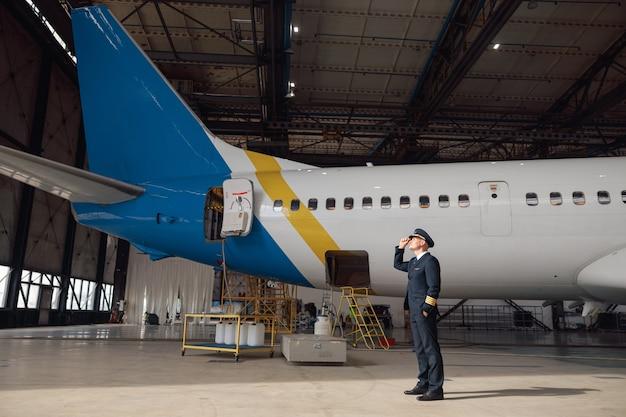 Trotse piloot in uniform kijkt weg, past zijn hoed aan en staat voor een groot passagiersvliegtuig in de luchthavenhangar. vliegtuigen, beroep, transportconcept