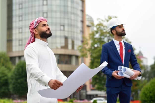 Trotse saoedische zakenman die over zijn ontwikkelingsstad kijkt die een blauwdruk houdt