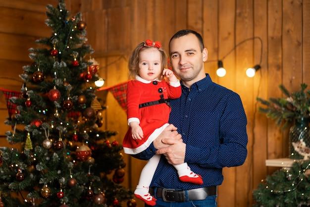 Trotse vader versiert de kerstboom terwijl hij zijn dochtertje in zijn armen houdt