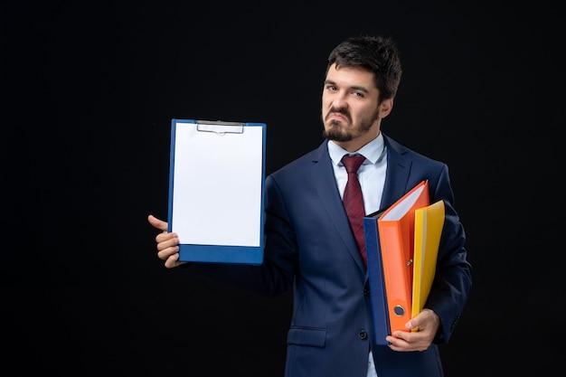 Trotse volwassene in pak die verschillende documenten vasthoudt en een ervan op een geïsoleerde donkere muur laat zien