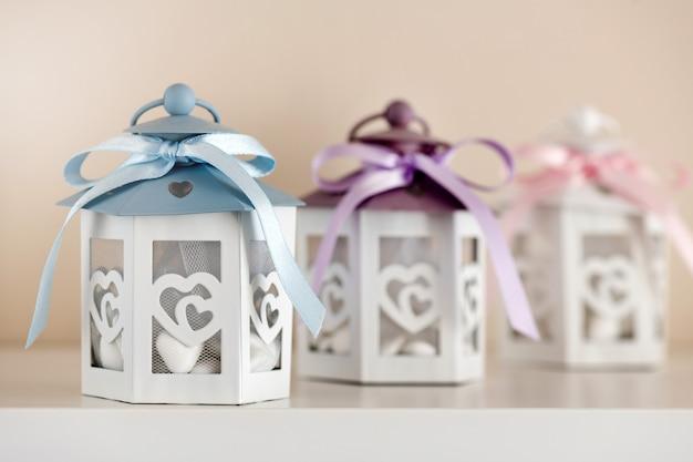 Trouwbedankjes, een klein cadeautje voor gasten in witte vintage lampendozen van papier met linten erop