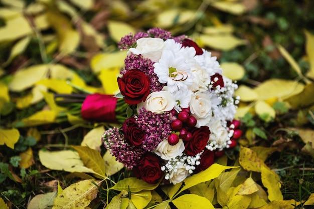 Trouwbloemen, trouwringen liggen op een bruidsboeket, boeket van rood en perzik, melkrozen en witte bloemen liggen op gele herfstbladeren, huwelijksceremonie