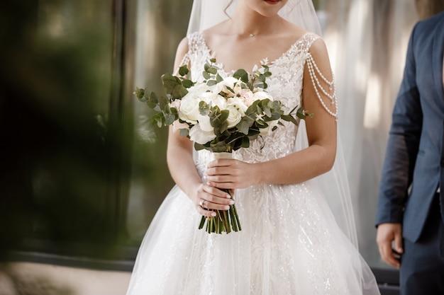 Trouwdag. bruidegom en bruid houdt een boeket van roze en witte bloemen. bruiloft decoratie.