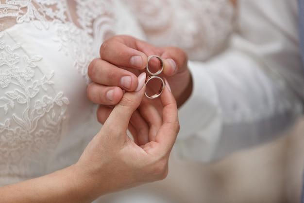 Trouwdag. bruiloft details close-up. twee gouden trouwringen in de handen van de pasgetrouwden met ruimte. net getrouwd