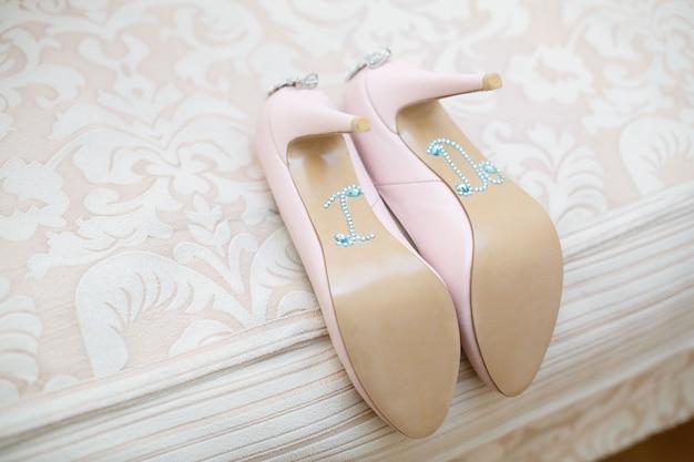 Trouwdag. bruiloft muur. huwelijksdetails en toebehoren. roze bruids schoenen met hoge hakken versierd met glanzende steentjes en stenen close-up. damesschoenen versierd het opschrift