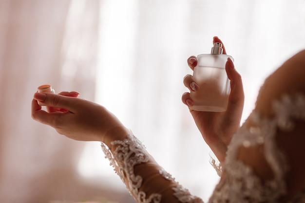 Trouwdag. de jonge bruid maakt zich thuis in de ochtend klaar. bruid die parfum op haar hals toepast.