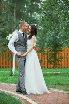 Trouwdag, een verliefd paar knuffelen en kussen in het park. man koestert mooie vrouw, verloving