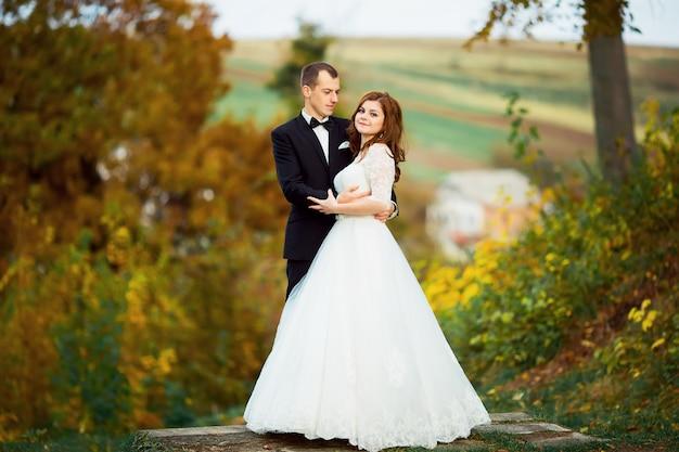 Trouwdag. gelukkige bruid en bruidegom. pasgetrouwden en liefde. afbeelding in een gele tint. zonnehuwelijk in het veld met zonnebloemen. gelukkig pasgetrouwde stel op hun trouwdag. gelukkig stel. lachende gezichten.