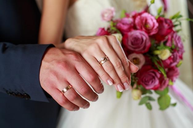 Trouwdag. jonggehuwden op de huwelijksceremonie. handen van bruid en bruidegom met gouden trouwringen