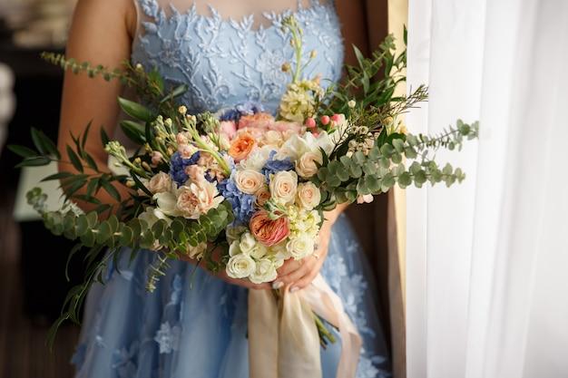 Trouwdag. mooie bruid in blauwe trouwjurk met boeket bloemen in rustieke stijl.